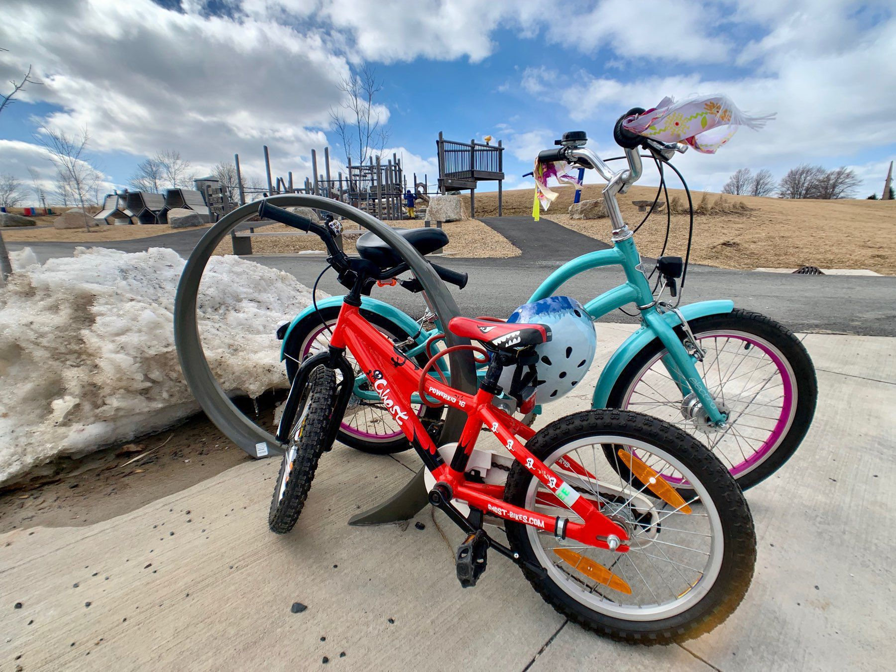Two children's bicycles outside of playground