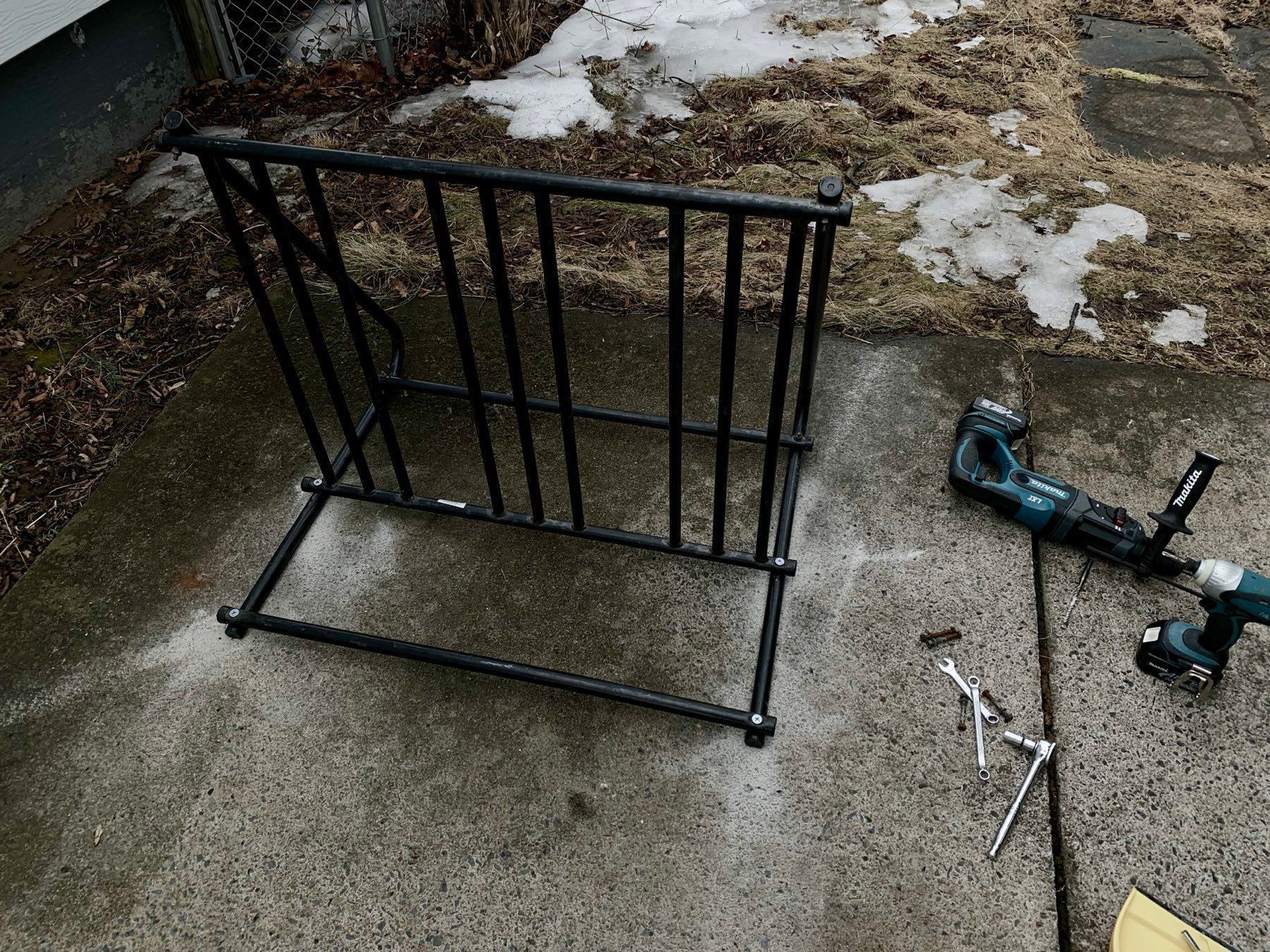 A bike rack on a concrete driveway with tools around it