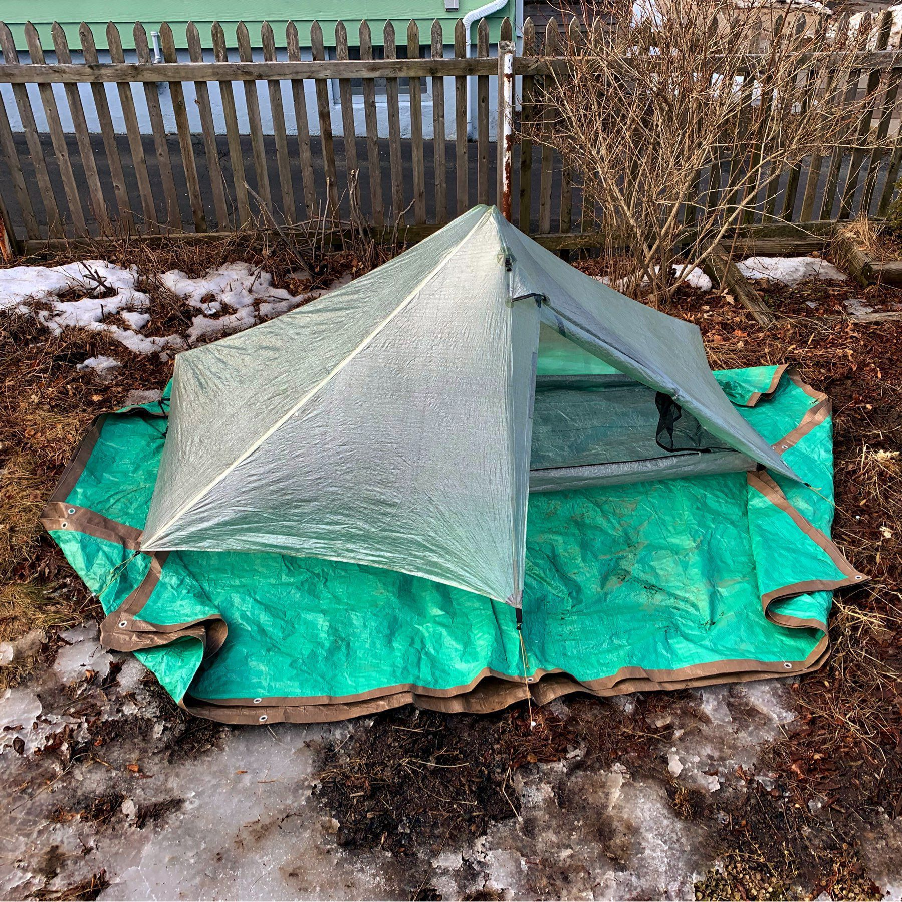 A tent in a backyard with the door open