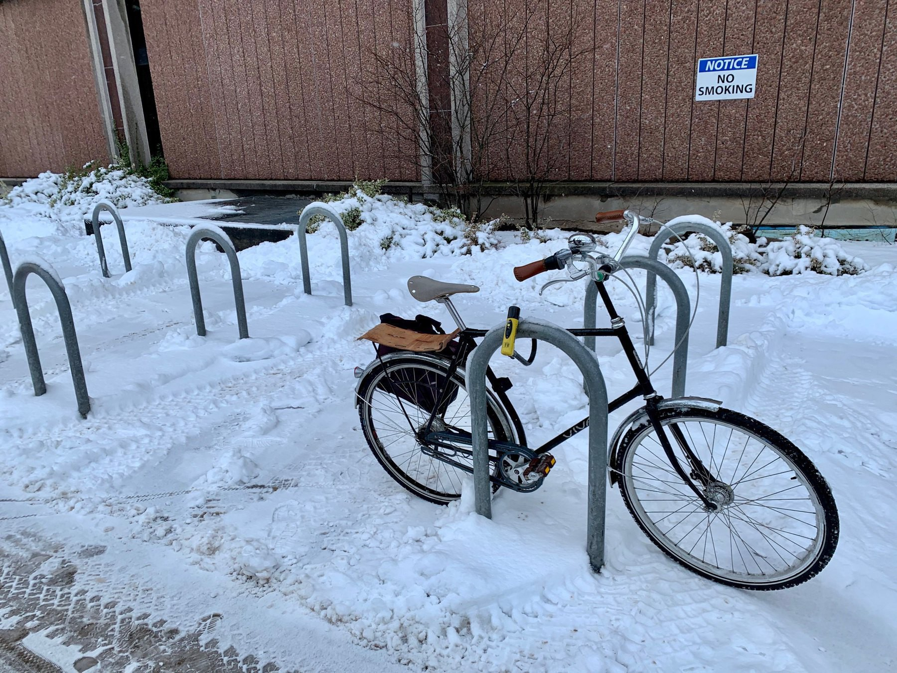 A bicycle parked at a set of bicycle racks that have snow plowed from inbetween them