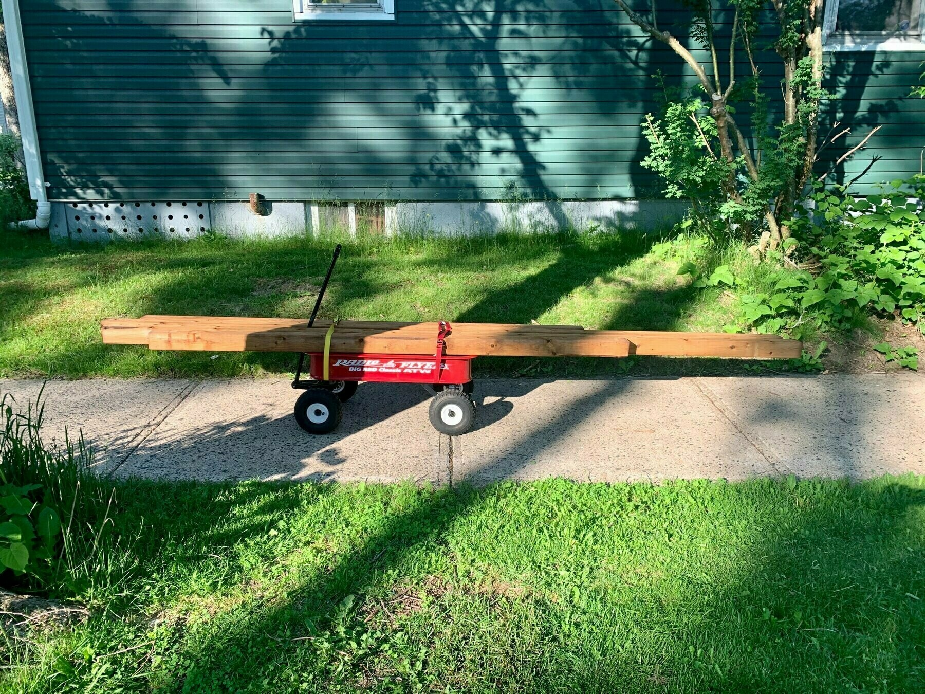 A kids wagon loaded with lumber.