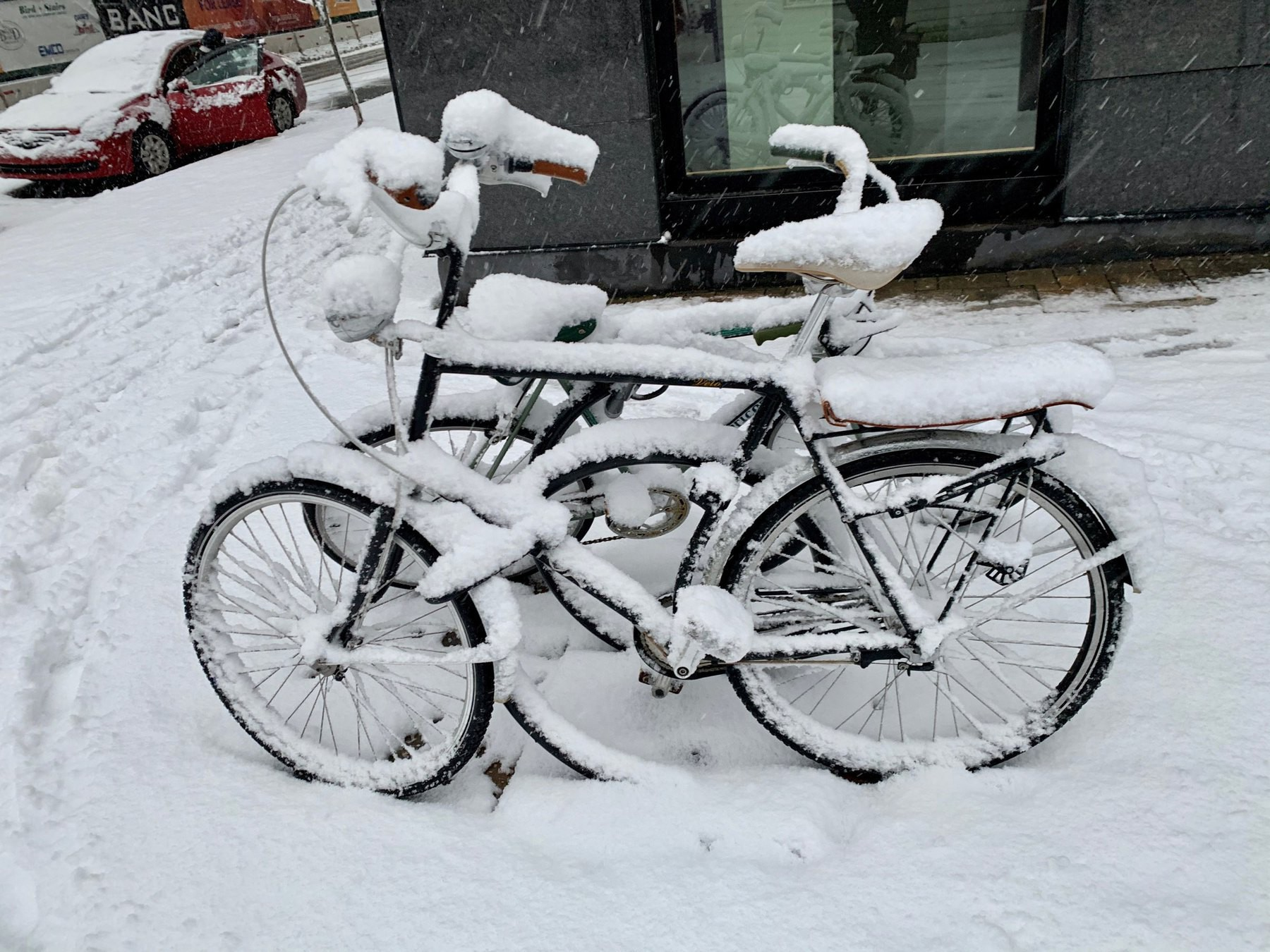 Snow-covered bicycles locked to a bike rack downtown