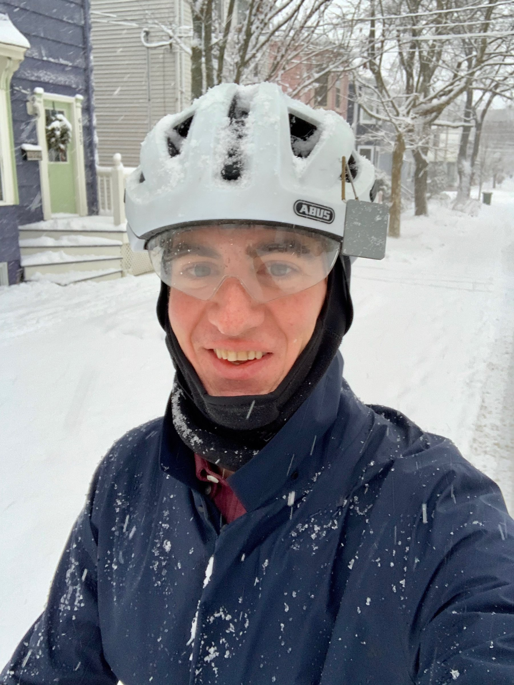 Selfie of a person wearing a bicycle helmet in the snow.