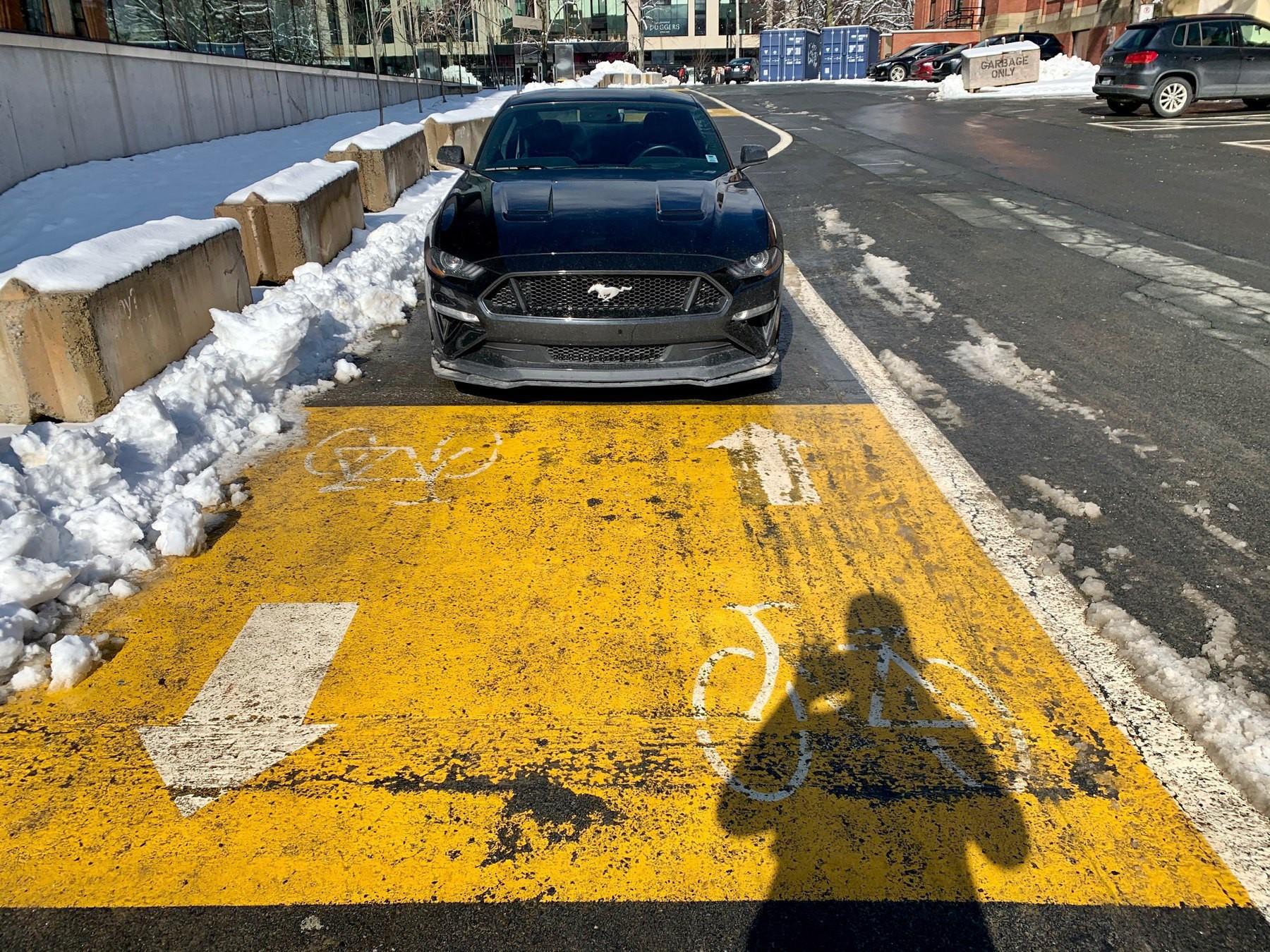 A car blocking a bicycle lane that has been cleared of snow.