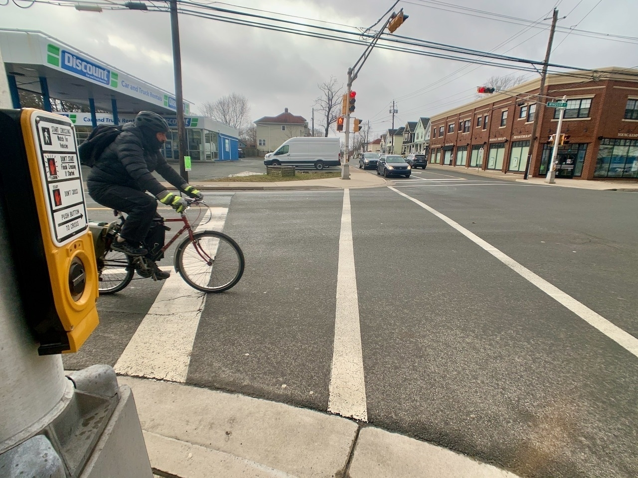 A Halifax crosswalk with a beg button and a cyclist.